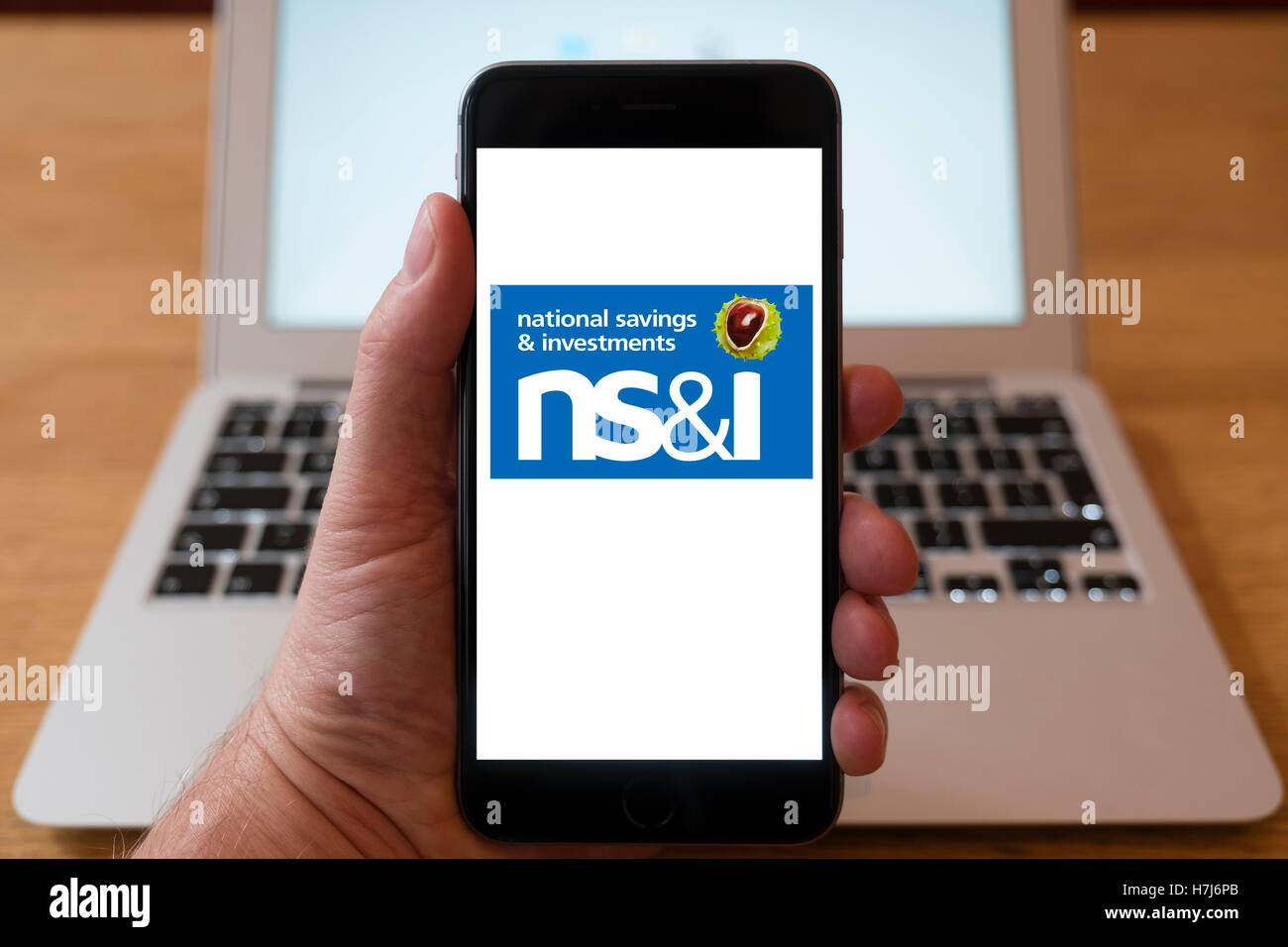 Using iPhone smart phone to display logo of NS&I  , National Savings and Investments . - Stock Image