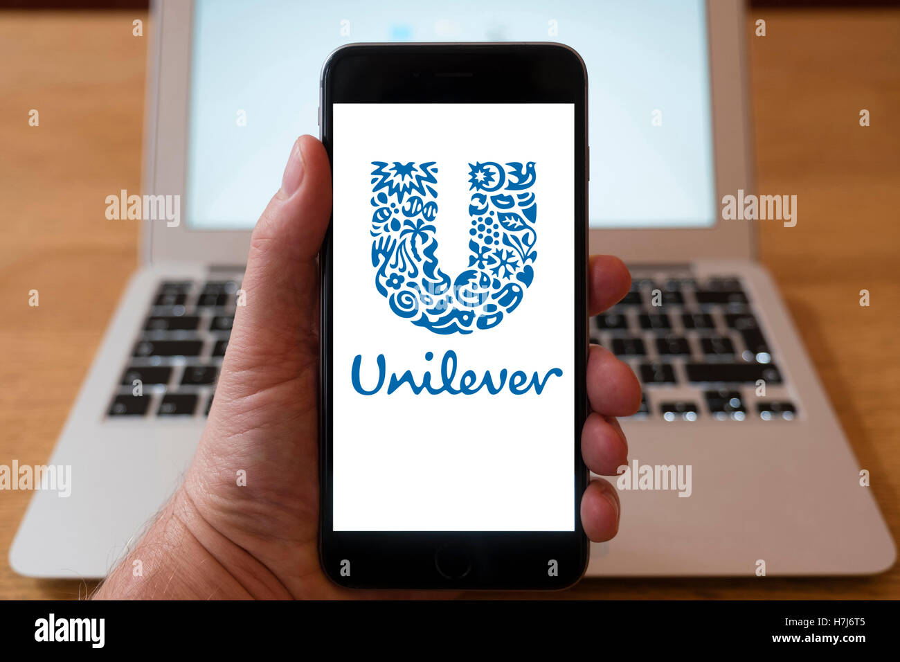Using iPhone smart phone to display logo of Unllever multinational conglomerate - Stock Image