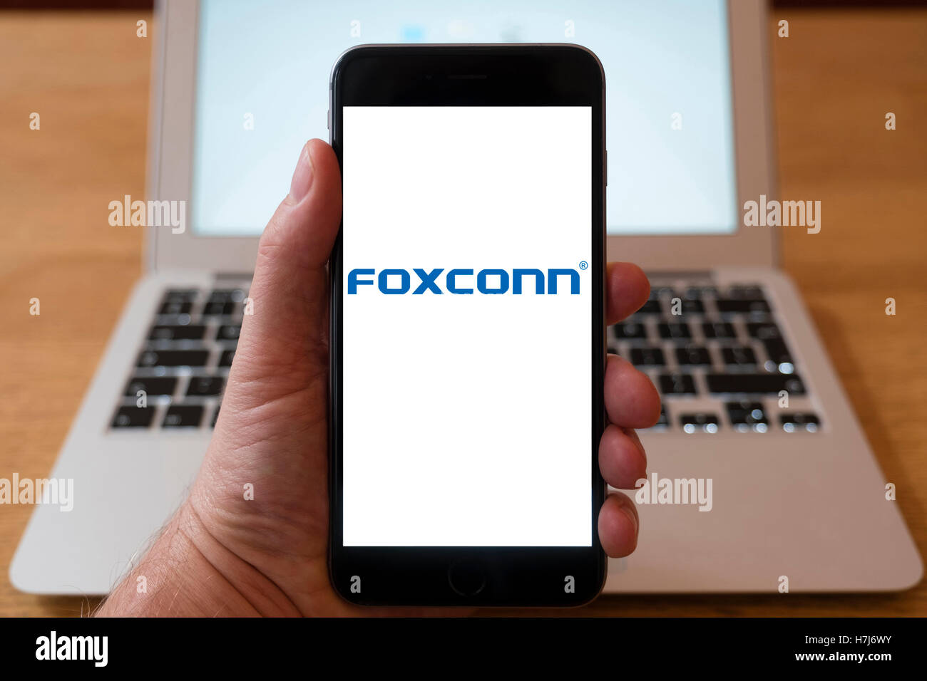 Using iPhone smartphone to display logo of Foxconn (Technology), Taiwanese multinational electronics contract manufacturing - Stock Image