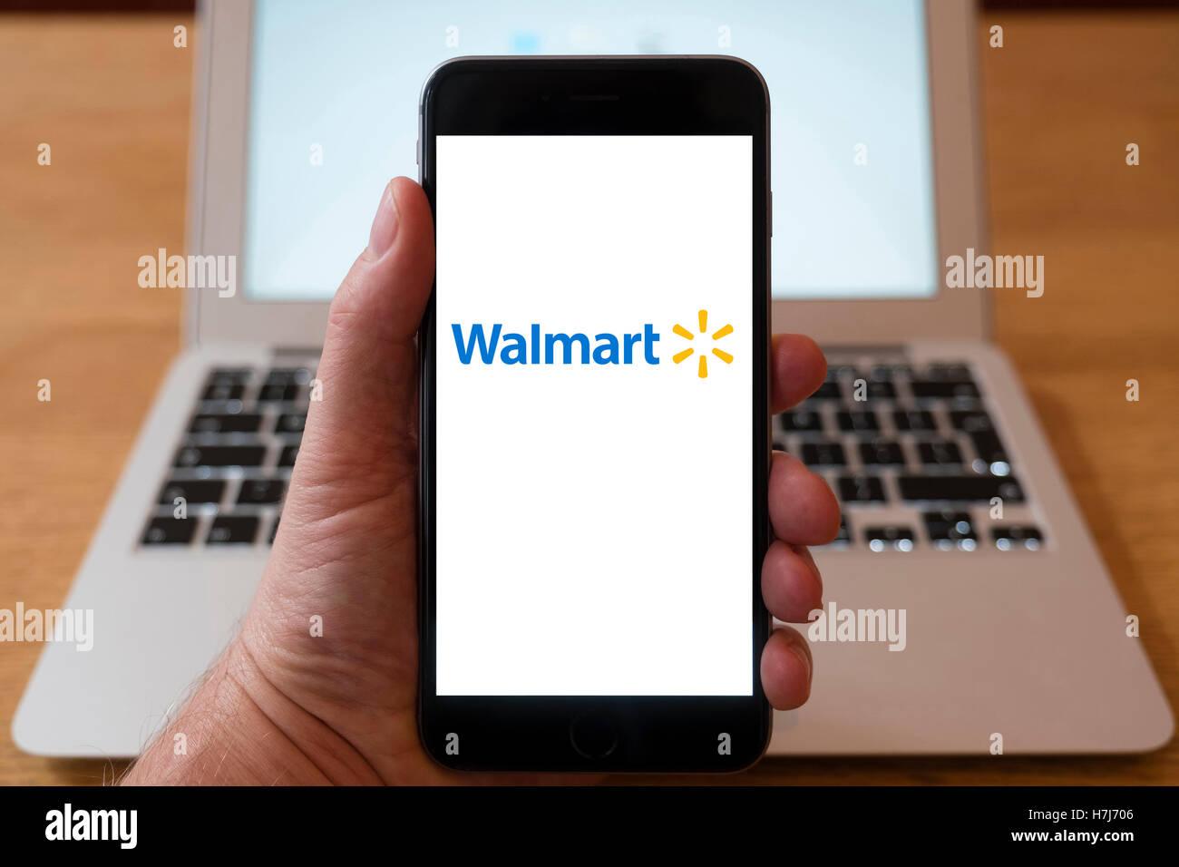 Using iPhone smartphone to display logo of Walmart , US multinational retail corporation - Stock Image