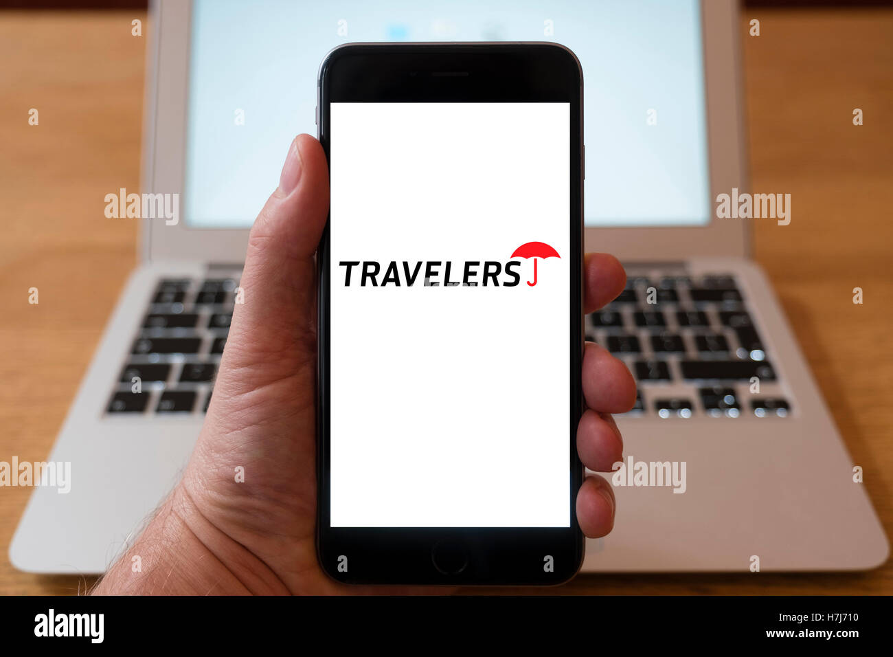 Using iPhone smartphone to display logo of Travellers insurance company - Stock Image
