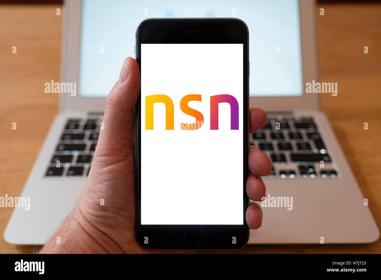 Using iPhone smartphone to display logo of Nokia Siemens Networks, multinational data networking and telecommunications - Stock Image