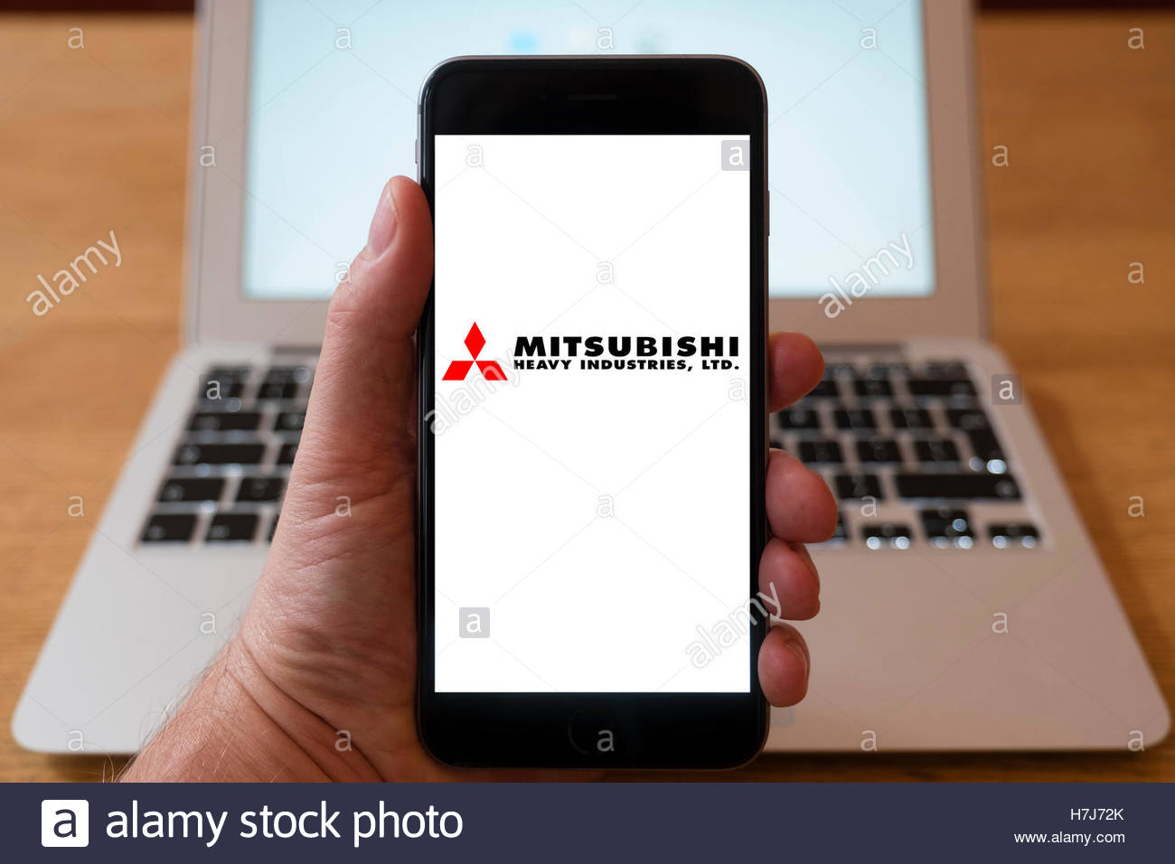 Using iPhone smartphone to display logo of Mitsubishi Heavy Industries - Stock Image