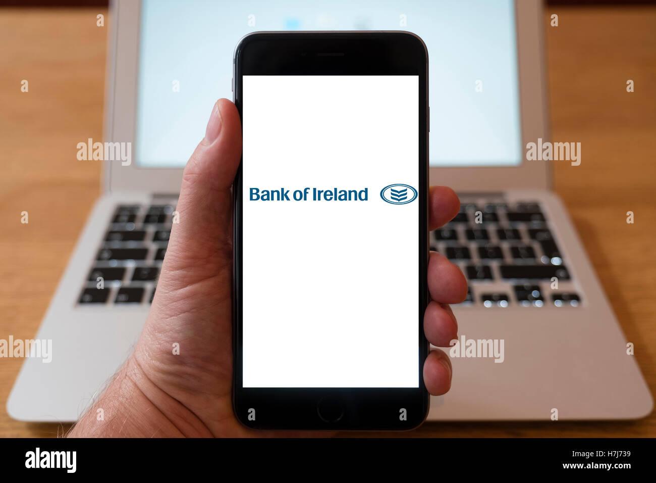 Using iPhone smartphone to display logo of Bank of Ireland - Stock Image