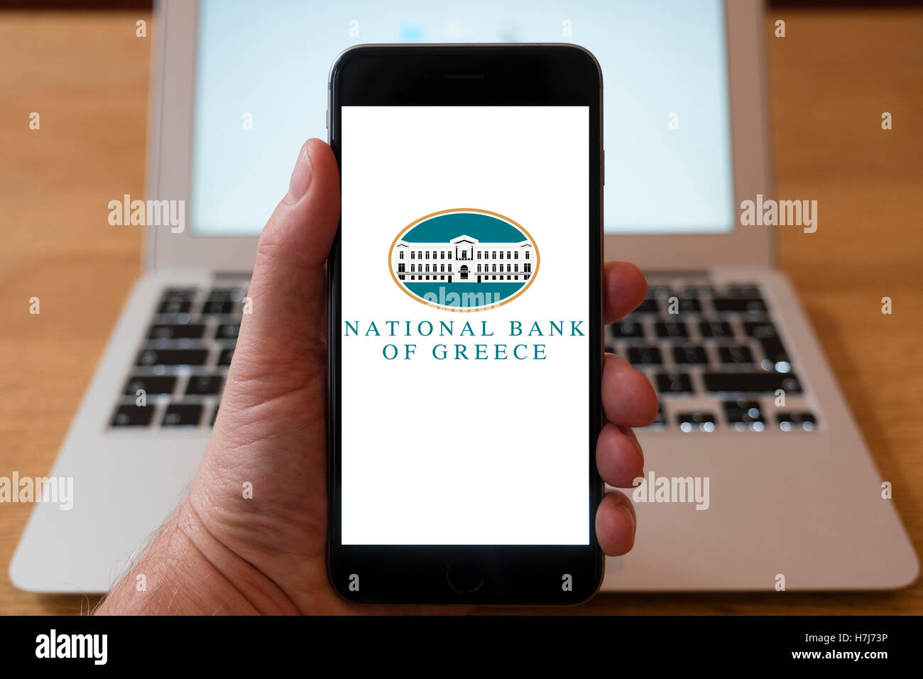 Using iPhone smartphone to display logo of National Bank of Greece - Stock Image