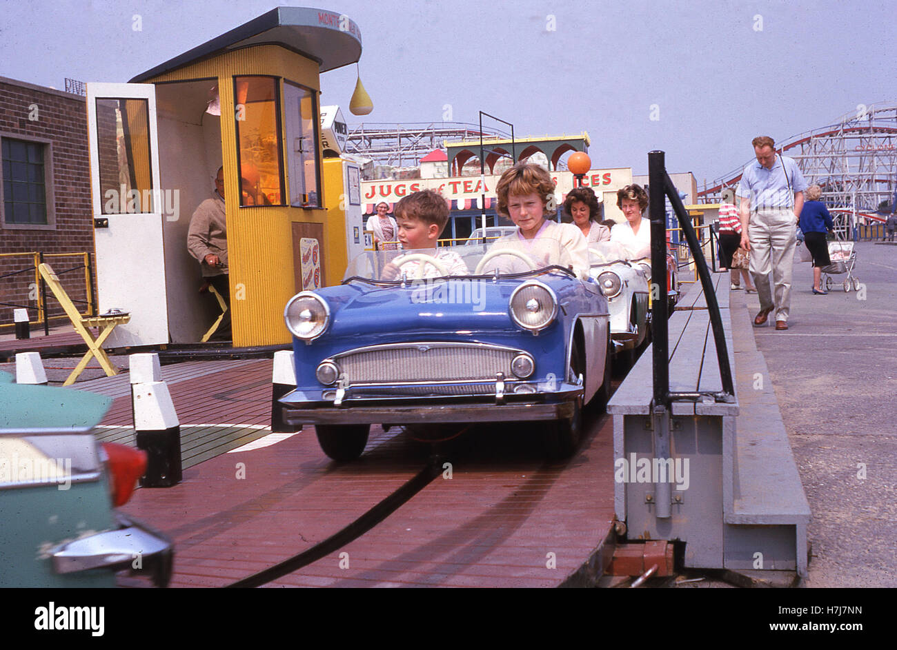 England, 1960s, two young children ride on a toy car at a British seaside funfair. In the background, a stall advertising - Stock Image