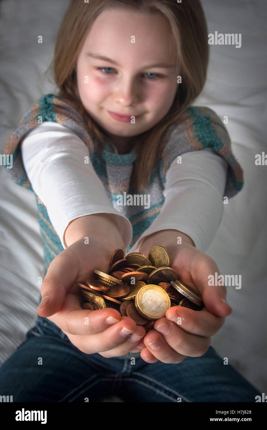A young girl with her Euro savings. - Stock Image