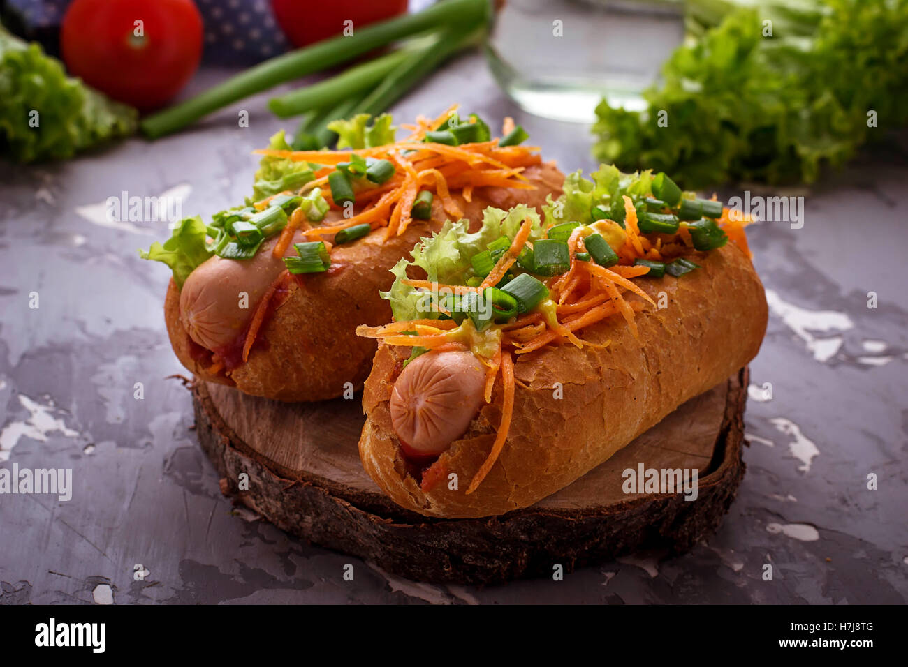 Hot dog with sausage, carrot, onion, lettuce. Selective focus - Stock Image