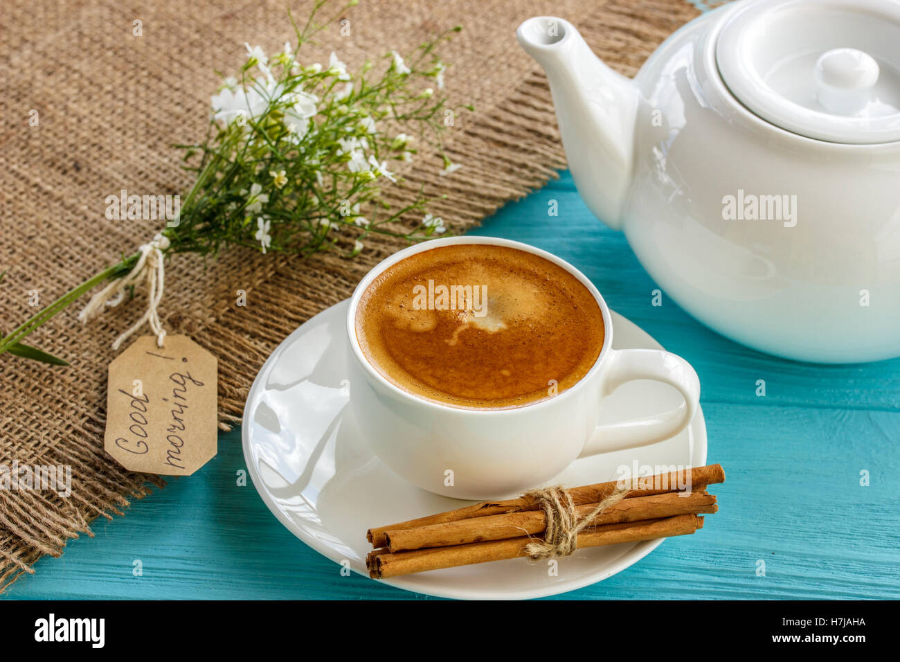 Coffee mug with white flowers and notes good morning on blue rustic table from above, breakfast - Stock Image
