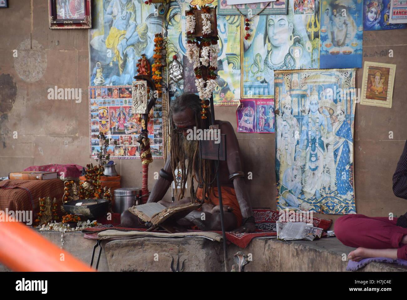 Indian sadhu sitting and reading with images of indian gods in Varanasi, Uttar Pradesh, India - Stock Image
