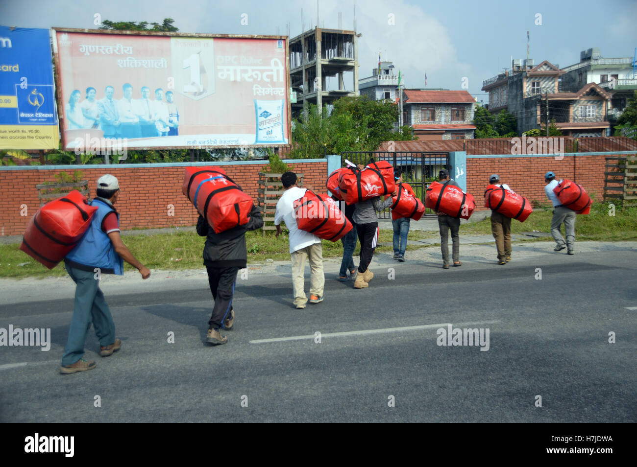 Porters Carrying Holiday Makers Bags Across a Road from Pokhara Airport to an Awaiting Bus, Nepal, Asia. - Stock Image