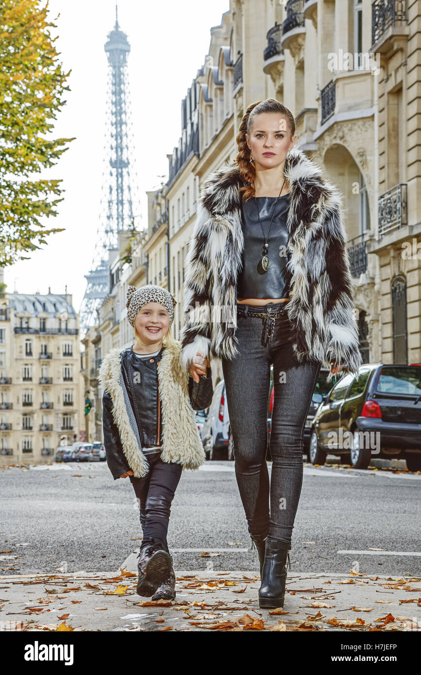 Boiling hot trendy winter in Paris. Full length portrait of modern mother and daughter in Paris, France going forward - Stock Image