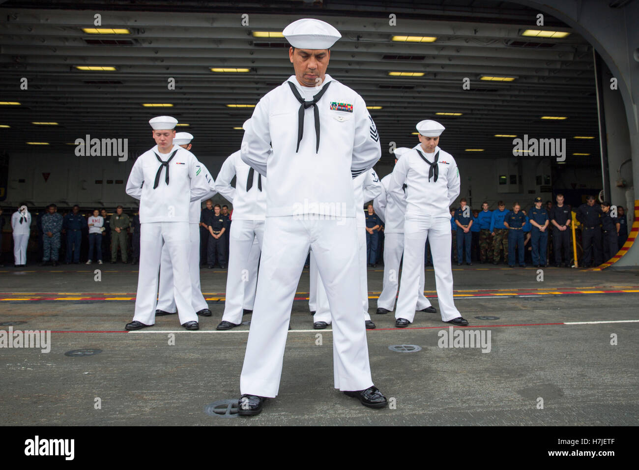 U.S. Navy sailors bow their heads in prayer during a burial at sea ceremony aboard the USN Wasp-class amphibious - Stock Image
