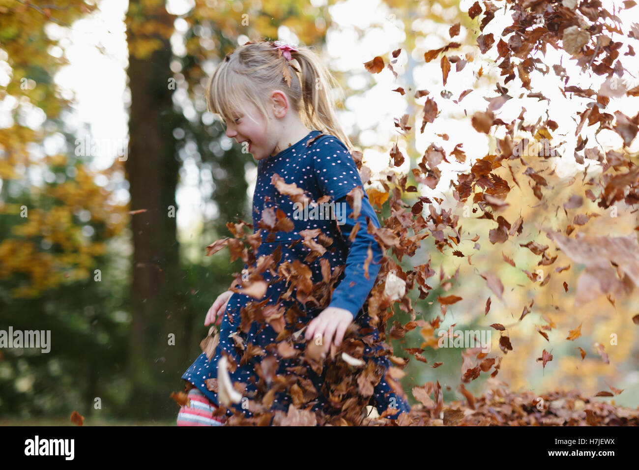 Happy autumn. Little girl playing in dry leaves pile in autumn park. - Stock Image