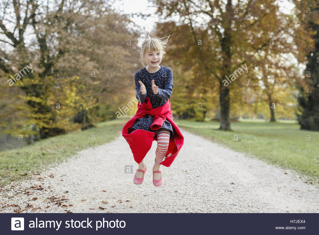 Happy autumn. Little girl in red coat jumping in autumn park. - Stock Image