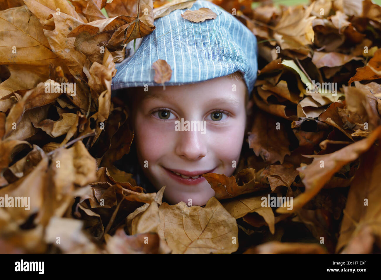 Happy autumn. Boy in retro flat cap looking out of dry leaves pile in autumn park. - Stock Image