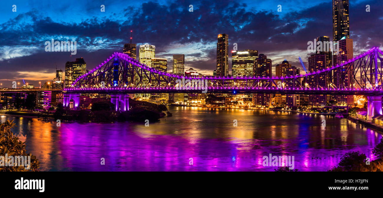Vibrant night time panorama of Brisbane city with Story Bridge - Stock Image