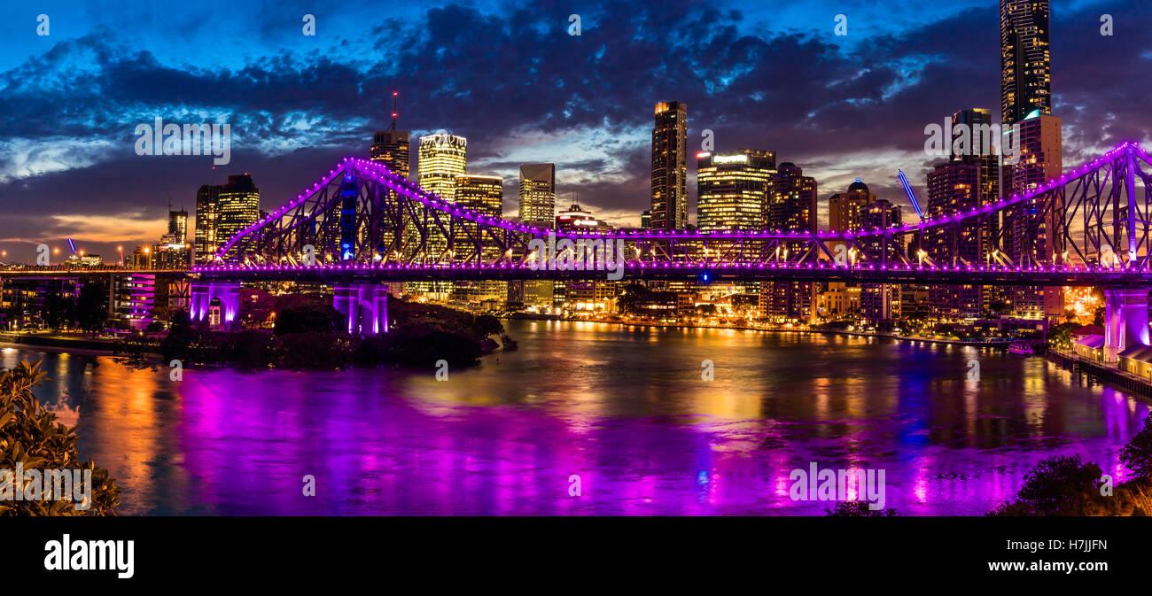 Vibrant night time panorama of Brisbane city with Story Bridge - Stock Image