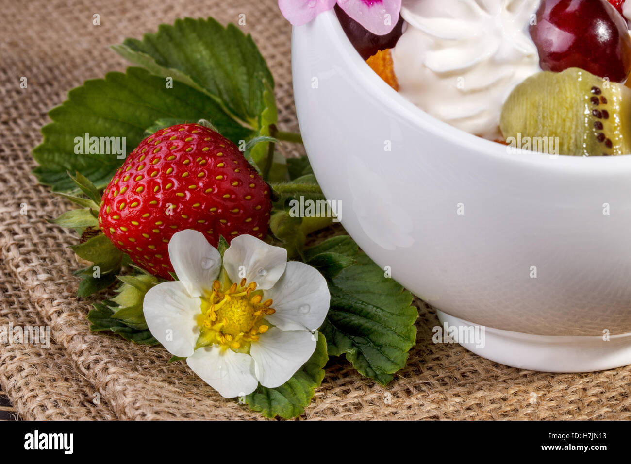Fruit salad closeup with  strawberry, orange, kiwi and cream  on an old wooden board - Stock Image