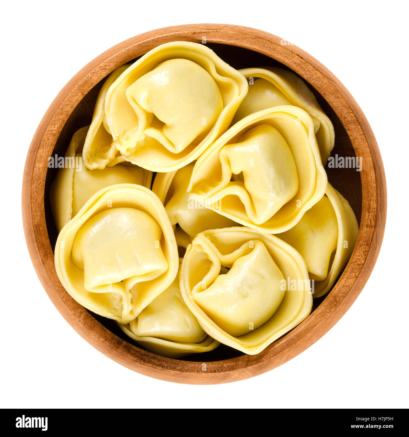 Tortelloni pasta in wooden bowl. Ring-shaped stuffed Italian dumplings with same shape as tortellini, but larger. Stock Photo