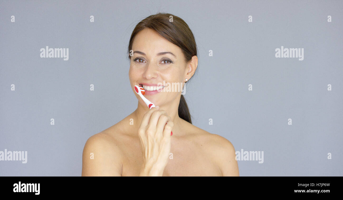 Attractive smiling woman brushing her teeth - Stock Image