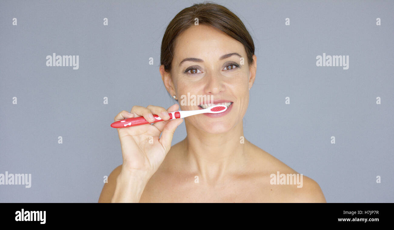 Healthy young woman cleaning her teeth - Stock Image