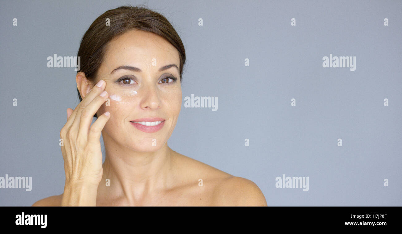 Beautiful young woman applying face cream - Stock Image