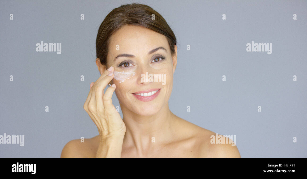Gorgeous young woman applying face cream - Stock Image