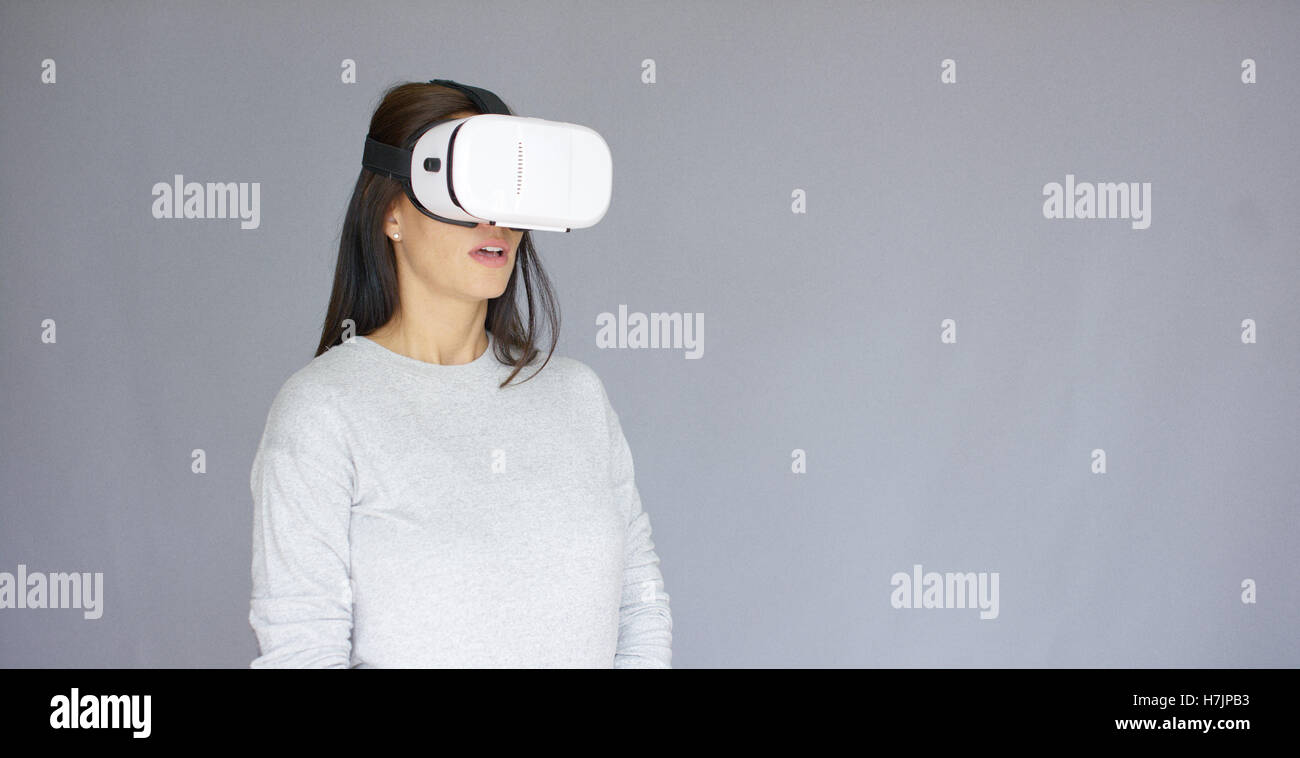Excited woman watching something on her virtual reality helmet - Stock Image