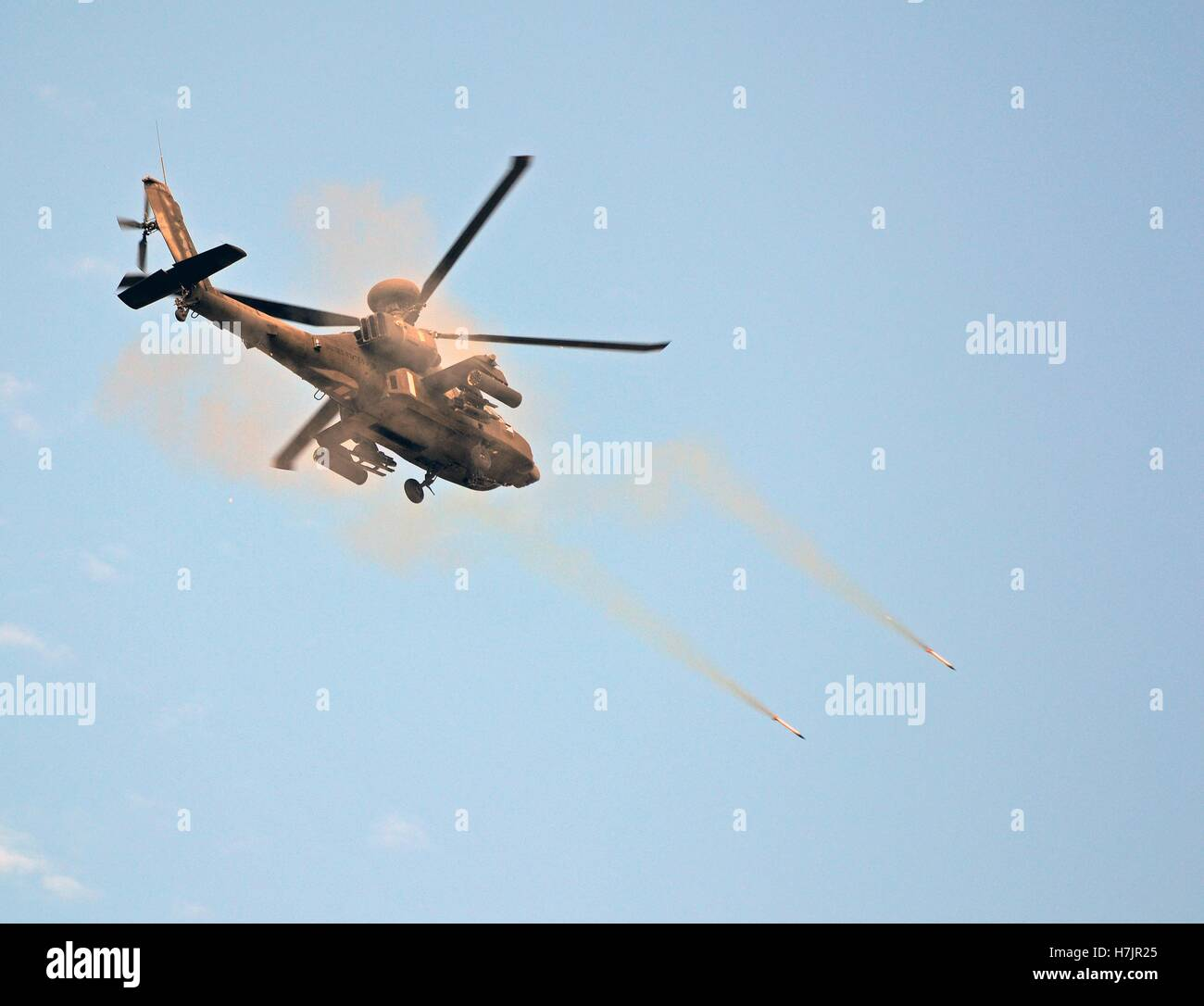 An AH-64 Apache attack helicopter fires simulation missiles during an aerial gunnery exercise September 9, 2014 - Stock Image