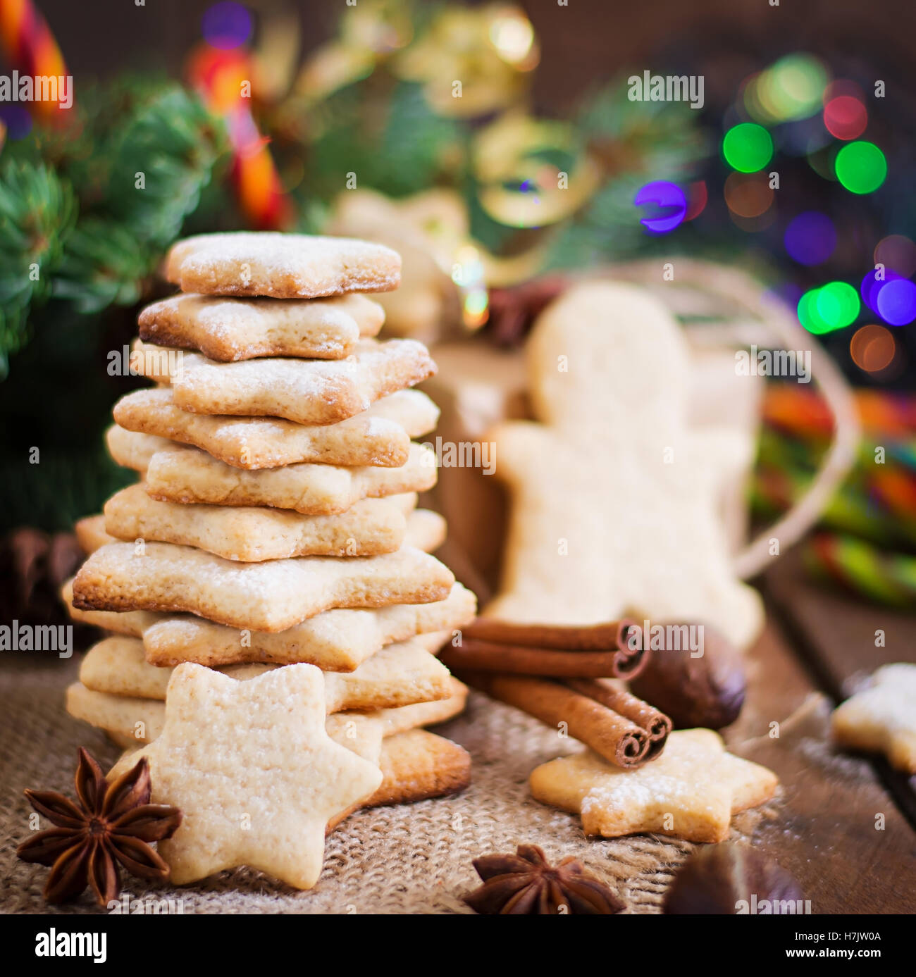 Christmas cookies and tinsel on a dark wooden background - Stock Image