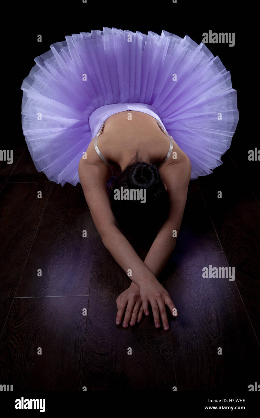 Ballerina wearing tutu stretched out on floor. Stock Photo