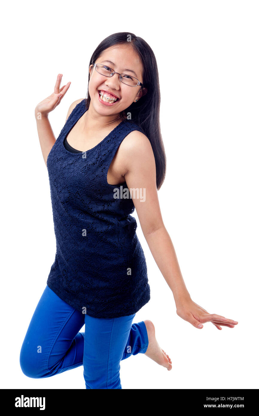 Cute Asian girl in braces striking a confident pose, isolated on white. - Stock Image