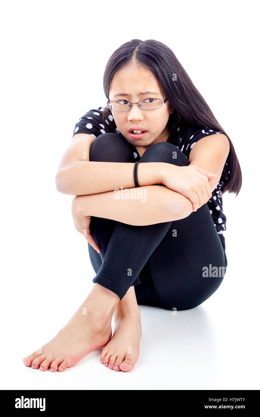 Worried Asian tween with a distressed and frightened look - Stock Image