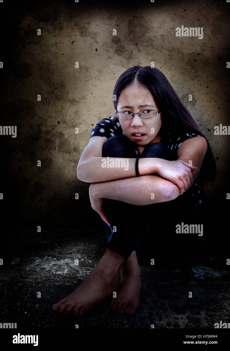 Distressed and frightened Asian tween, with copy space. - Stock Image