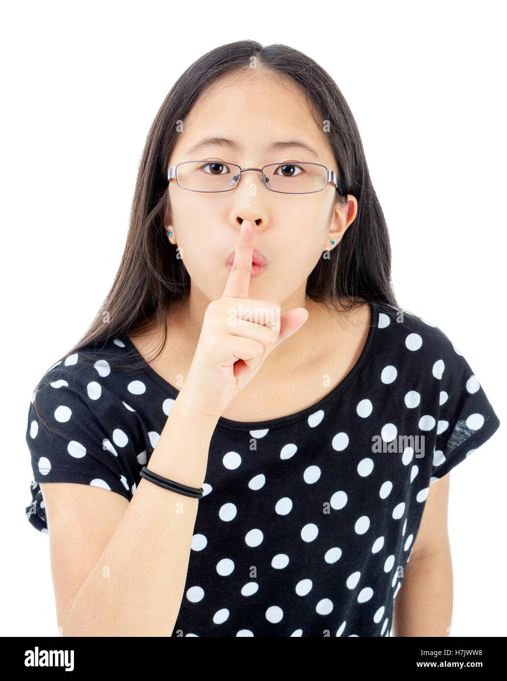 Asian tween with finger on lips in a gesture to keep silent - Stock Image