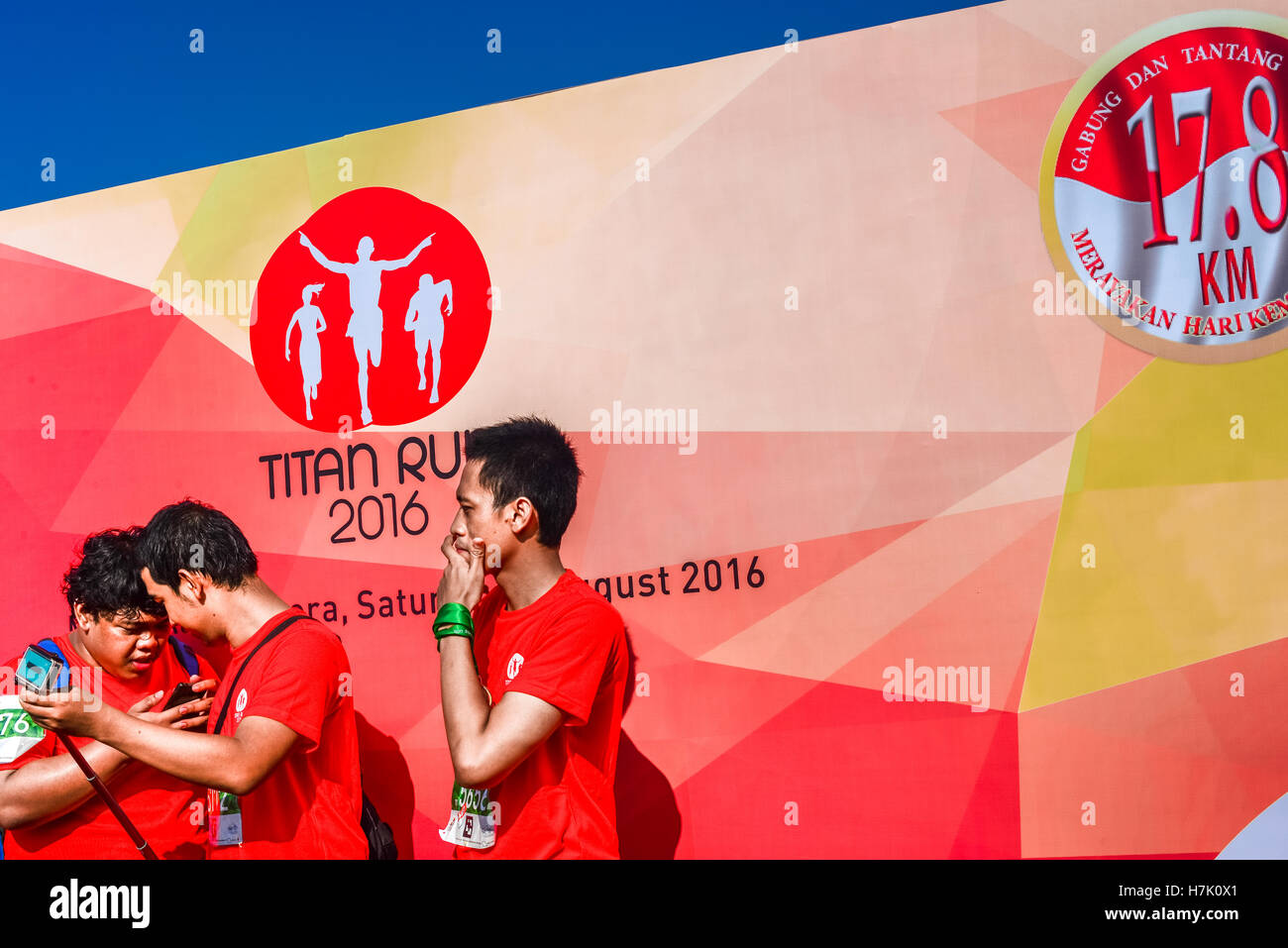 Young men about to take self-portrait photo with podium backdrop as background in Titan Run running event in Indonesia. - Stock Image