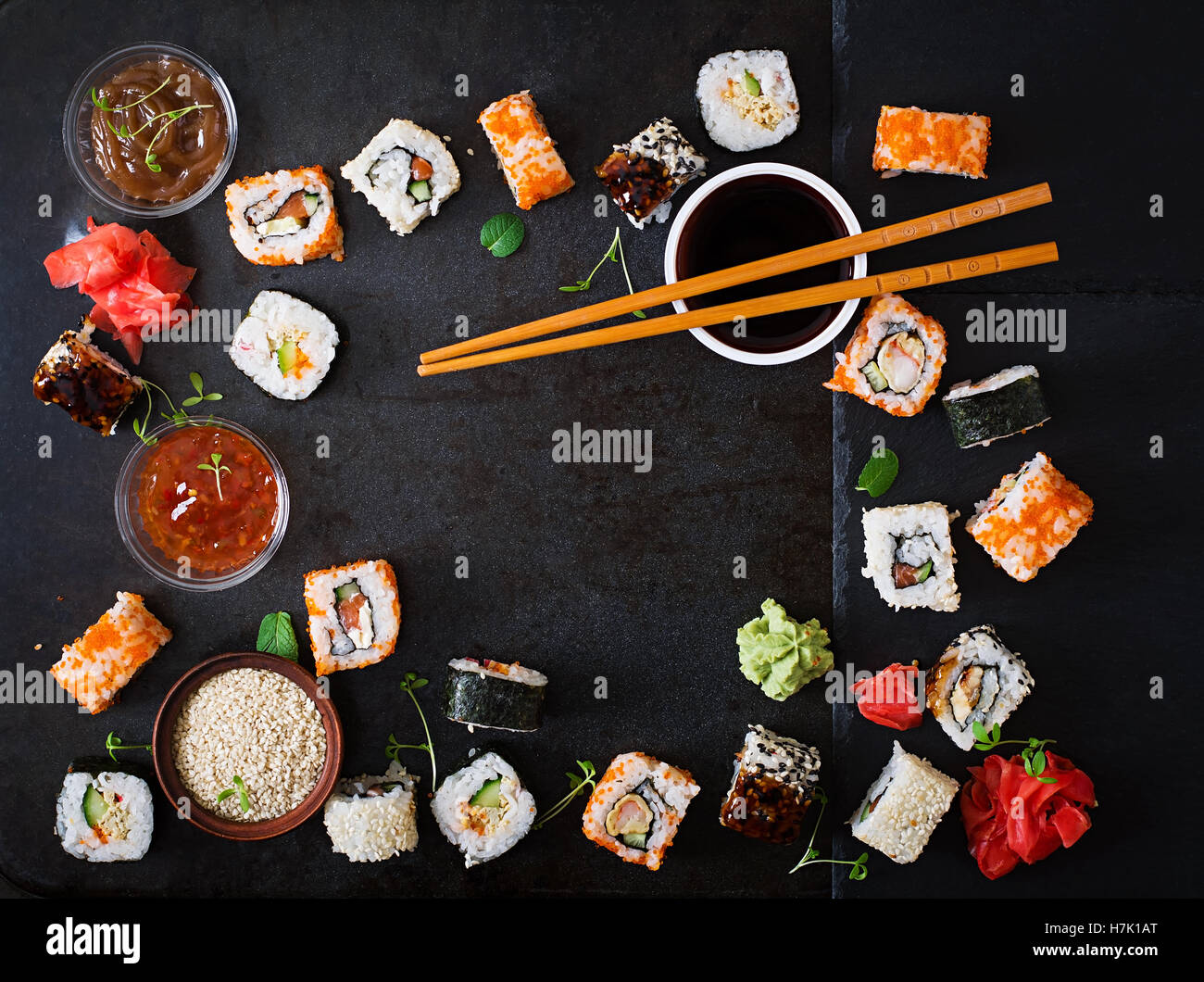 Traditional Japanese food - sushi, rolls and sauce on a dark background. Top view - Stock Image