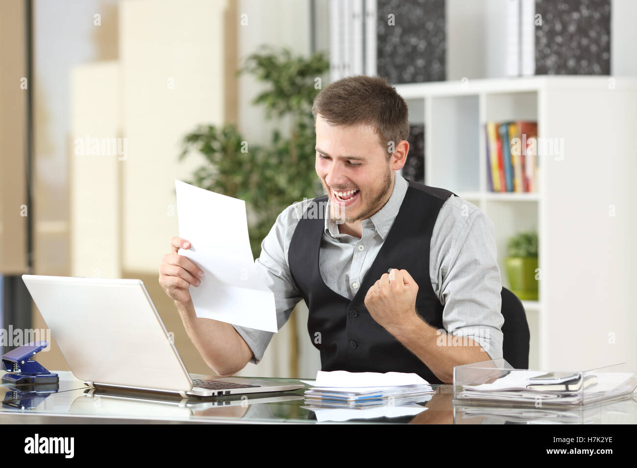 Excited businessman reading good news in a a letter in a desktop at office - Stock Image