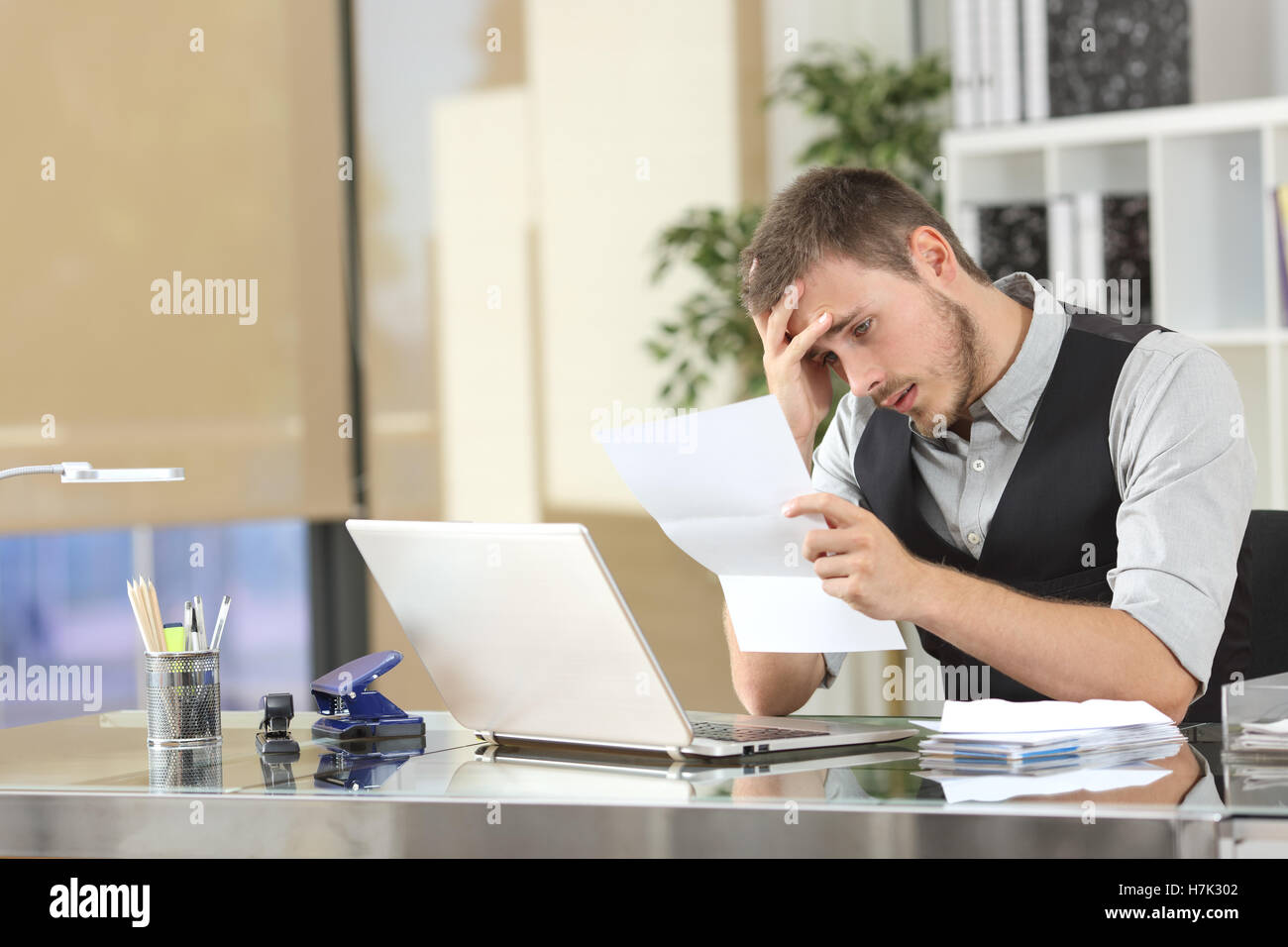 Sad businessman reading bad news in a letter sitting in a desk at office - Stock Image