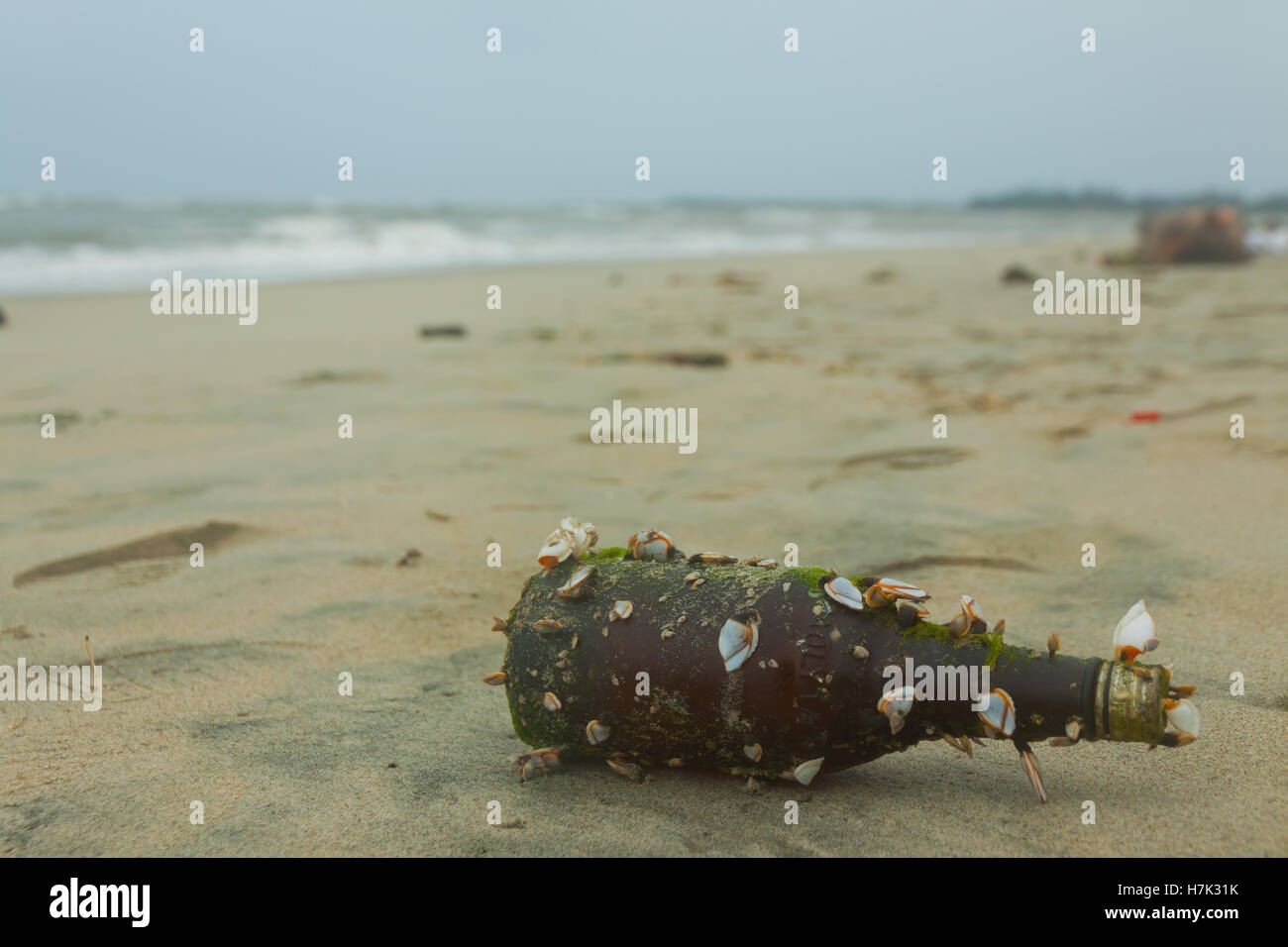 Old Dirty Bottle on the sand Beach - Stock Image
