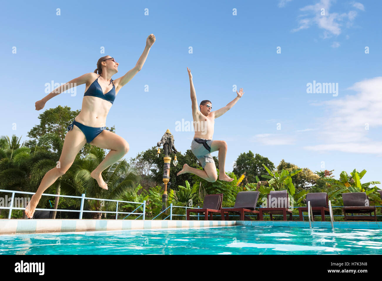 Two Friends Enjoy Jumping In The Swimming Pool At A Tropical Hotel Resort