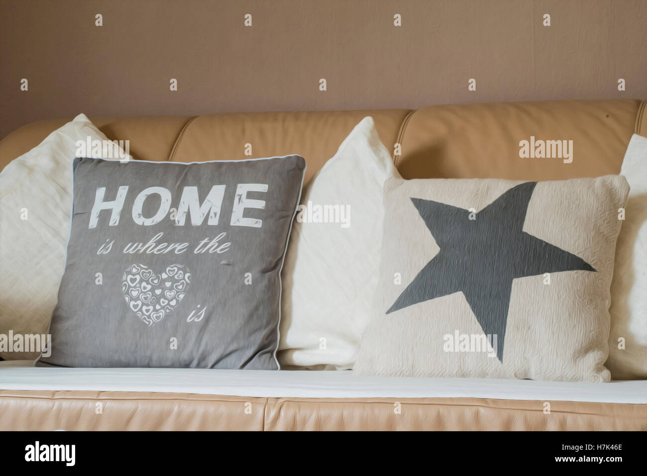 Home is where the heart pillow on sofa couch - Stock Image