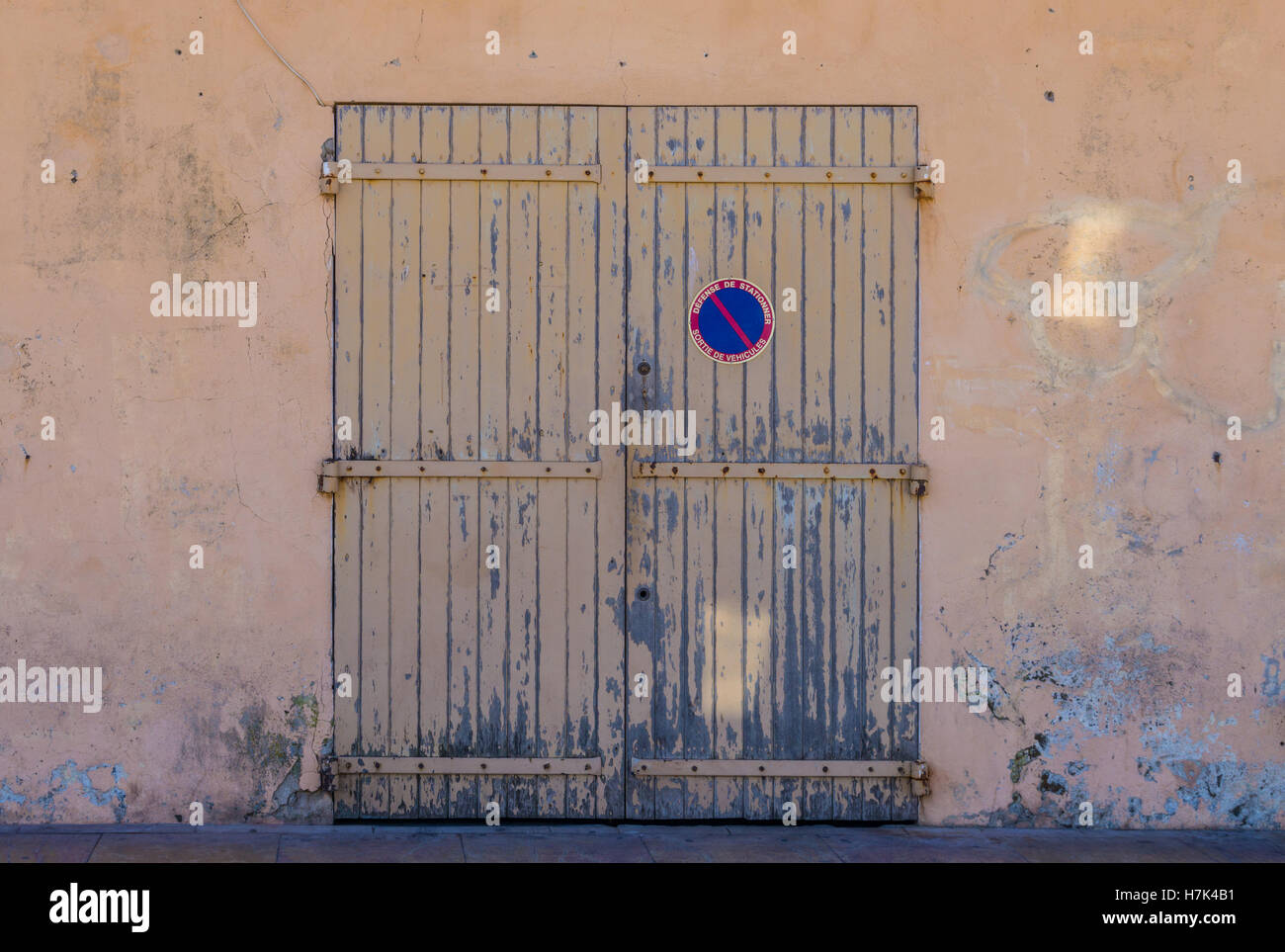 An old painted wooden door in a painted wall with 'Defense de Stationner Sortie de Vehicules' in French. - Stock Image