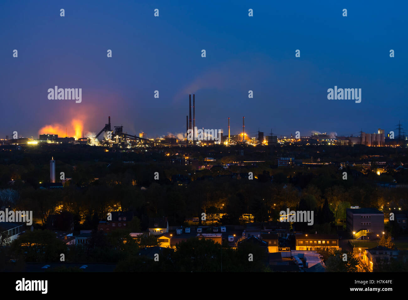 View of a large coking and steel plant in Duisburg, Germany in the night with tapping resulting in the red glow. - Stock Image