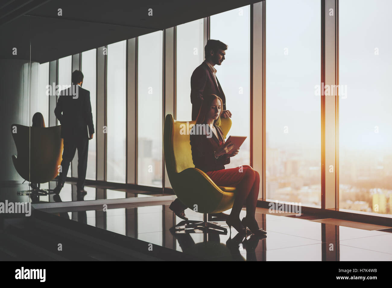 Young smiling successful man entrepreneur in formal business suite thoughtfully standing near yellow armchair - Stock Image