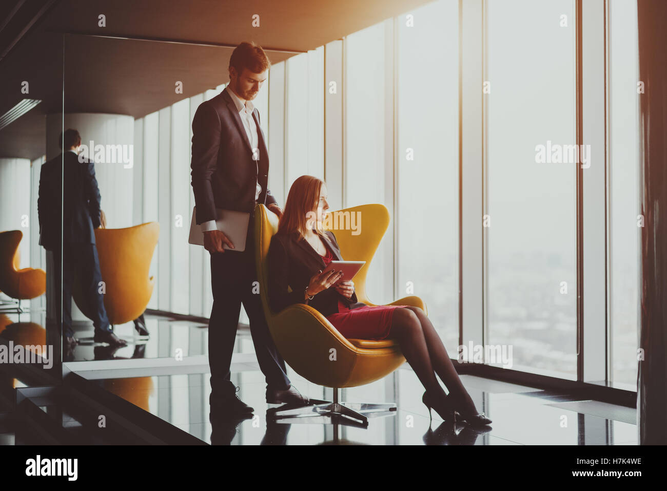 Young serious successful man entrepreneur in formal business suite with a beard standing near his colleague with - Stock Image