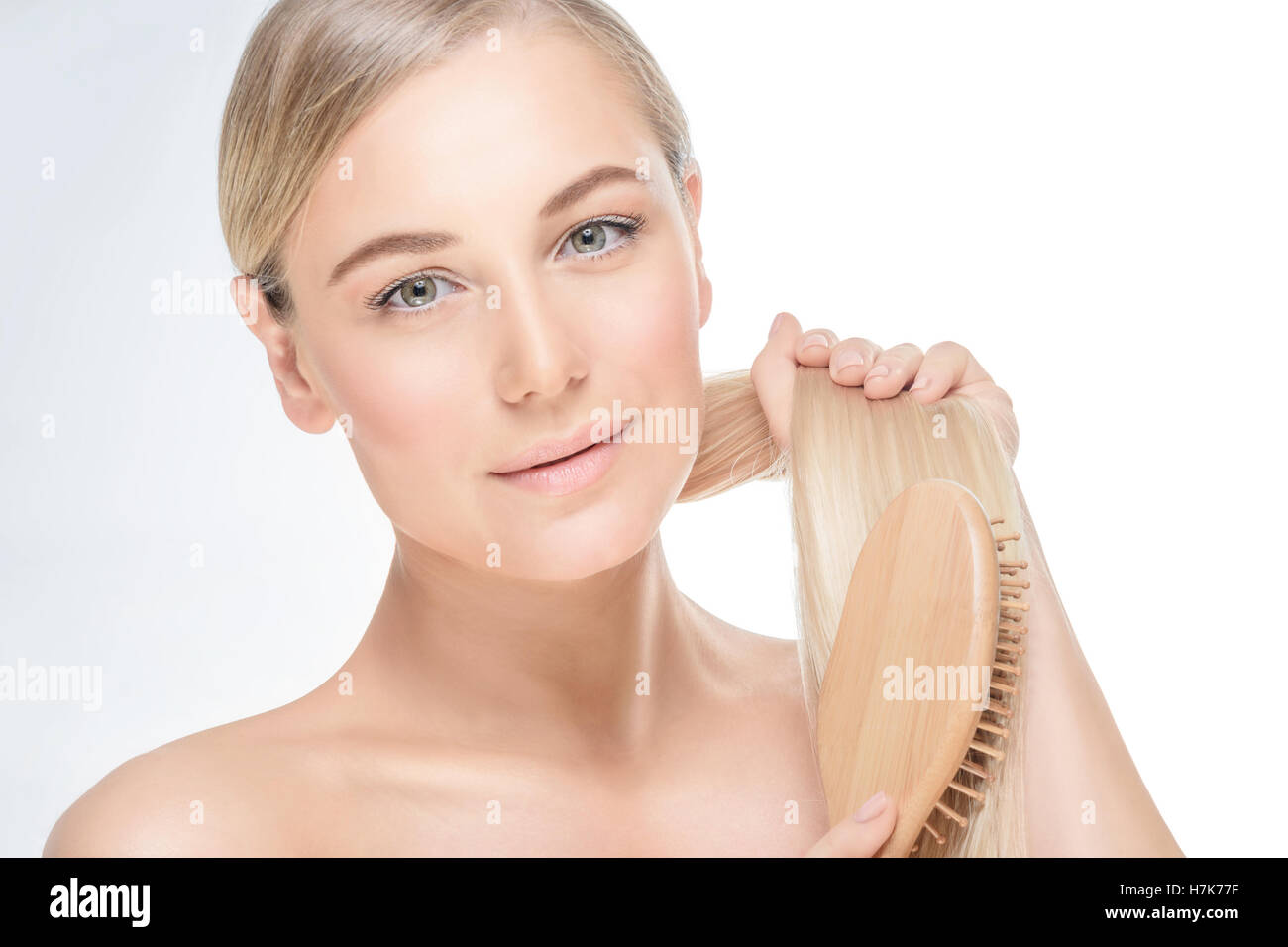 Portrait of a gentle blond female combing her hair isolated on grey white background, treatment in spa salon, healthy - Stock Image