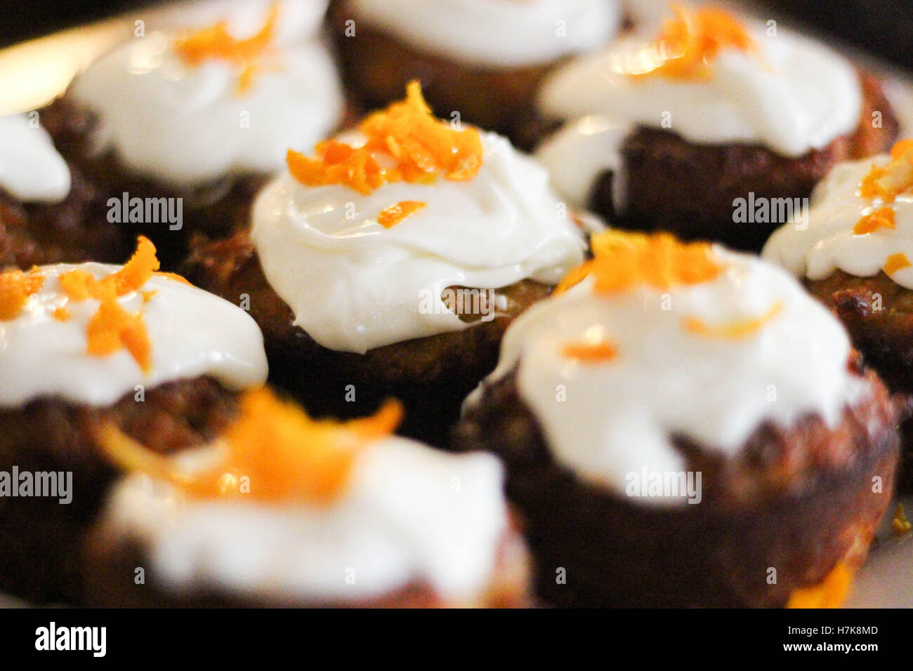 orange muffins with cream cheese frosting and orange zest - Stock Image