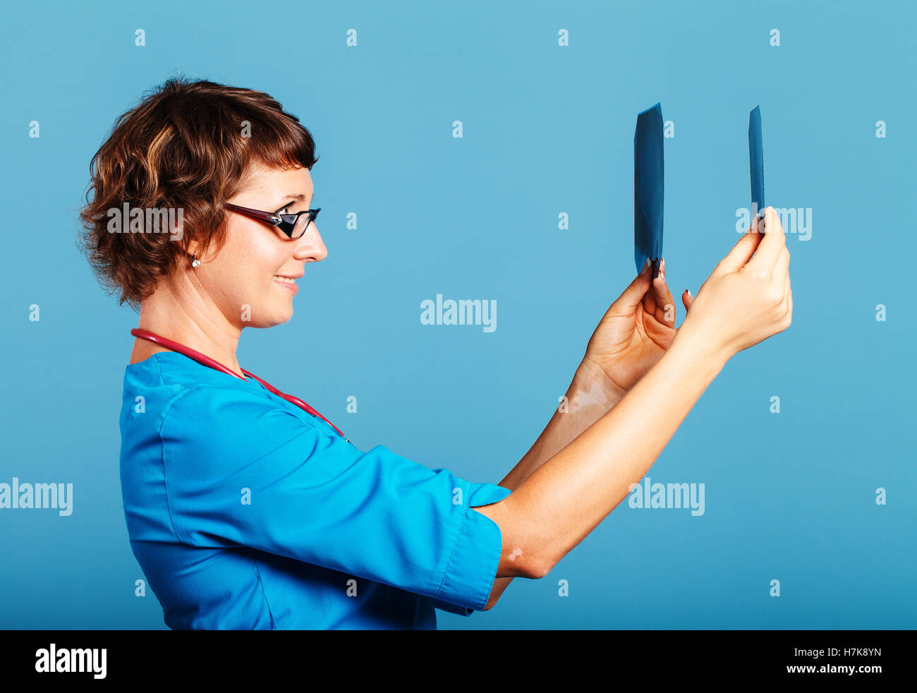 Doctor looking X-ray images of patients, shot in studio on a blue background - Stock Image